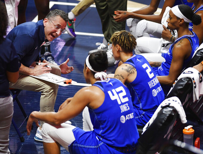 Connecticut Sun coach Curt Miller, left, gives instruction to the team in a huddle during a timeout during a WNBA basketball game against the Seattle Storm, Sunday, June 13, 2021, at Mohegan Sun Arena in Uncasville, Conn. (Sean D. Elliot/The Day via AP)