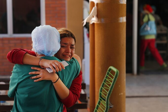 Laura Aguero, the niece of 38-year-old lawyer Arturo Benitez who spent 25 days in the ICU for COVID-19 at Clinicas Hospital, embraces a nurse after learning he died, in San Lorenzo, Paraguay, Friday, June 4, 2021. Aguero said the family spent almost $15,000 dollars on medication for him that was not provided by the hospital. (AP Photo/Jorge Saenz)