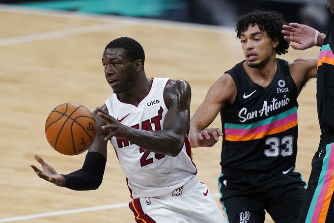 Miami Heat guard Kendrick Nunn (25) moves the pall past San Antonio Spurs guard Tre Jones (33) during the second half of an NBA basketball game in San Antonio, Wednesday, April 21, 2021. (AP Photo/Eric Gay)
