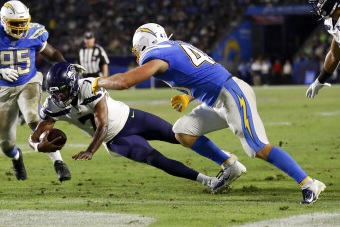 Seattle Seahawks quarterback Geno Smith, left, scores past Los Angeles Chargers linebacker Nick Dzubnar during the second half of an NFL preseason football game Saturday, Aug. 24, 2019, in Carson, Calif. (AP Photo/Gregory Bull)