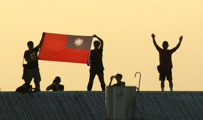 FILE - In this Sept. 14, 2014, file photo, locals on a warehouse rooftop display the national flag while watching Taiwan fighter jets practice during military exercises in Chiayi, central Taiwan. The Pacific island nation of Kiribati severed ties with Taiwan on Friday, Sept. 20. 2019, the second such loss for diplomatically isolated Taiwan in less than a week. (AP Photo/Wally Santana, File)