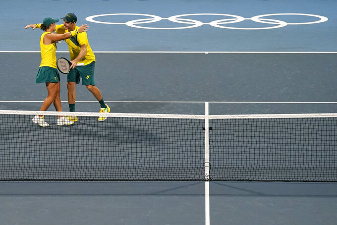 Ashleigh Barty, left, and John Peers, of Australia, celebrate after defeating Maria Sakkari and Stefanos Tsitsipas, of Greece, in a mixed doubles quarterfinal tennis match at the 2020 Summer Olympics, Thursday, July 29, 2021, in Tokyo, Japan. (AP Photo/Patrick Semansky)