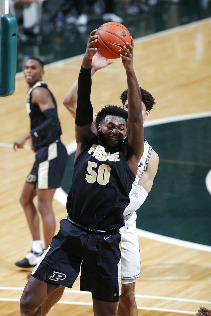Purdue's Trevion Williams (50) pulls down a rebound in front of Michigan State's Malik Hall during the second half of an NCAA college basketball game, Friday, Jan. 8, 2021, in East Lansing, Mich. (AP Photo/Al Goldis)