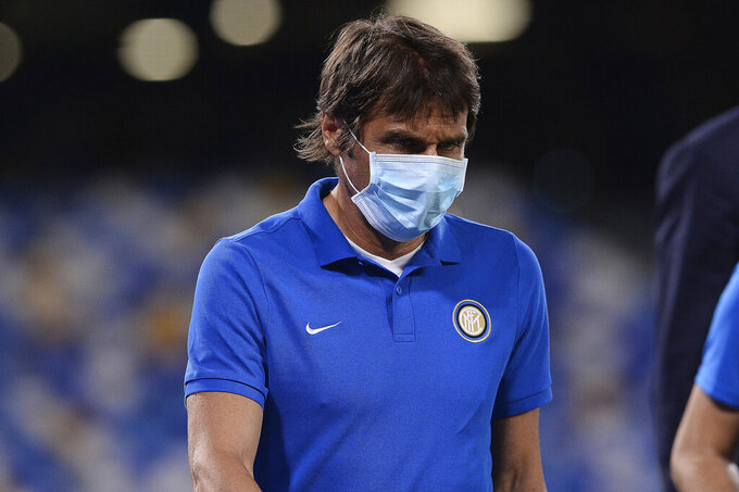 Inter Milan coach Antonio Conte enters the pitch prior to the Italian Cup second leg semifinal soccer match between Napoli and Inter Milan, at the Naples San Paolo Stadium, Italy, Saturday, June 13, 2020. The match is being played without spectators because of the COVID-19 restriction measures. (Cafaro/LaPresse via AP)