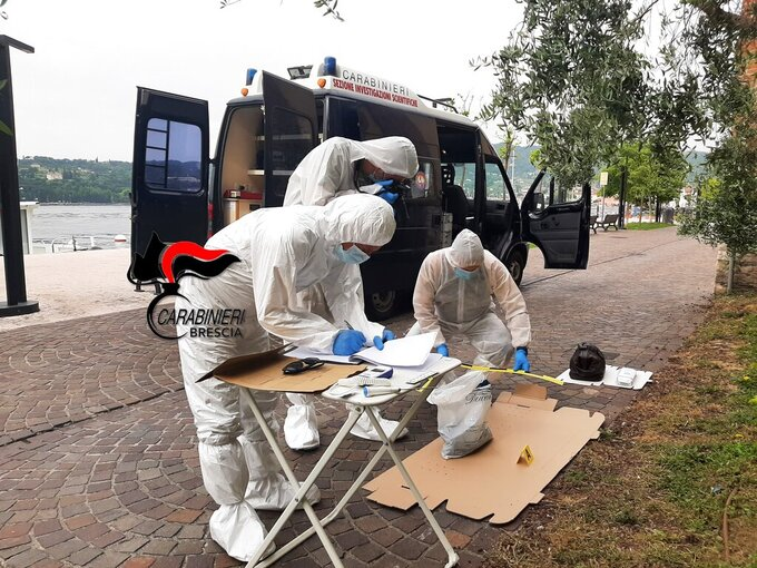 Italian forensic police stand by Lake Garda as they are investigating two German tourists from Munich for a boat collision which killed an Italian man and woman, on Lake Garda, northern Italy, Monday, June 21, 2021. Carabinieri paramilitary police on Monday didn't immediately give details. Italian media said the woman's body was found in the lake by Italian firefighter rescue divers on Sunday evening and that the man's body was found in their small boat earlier in the day. (Carabinieri via AP)