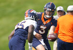 Denver Broncos quarterback Drew Lock, right, hands off the ball to running back Melvin Gordon as they take part in drills during an NFL football training camp at the team's headquarters Tuesday, Aug. 10, 2021, in Englewood, Colo. (AP Photo/David Zalubowski)