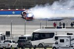 Fans look on as Sheldon Creed crashes in Turn 2 during a NASCAR Truck Series auto race at Texas Motor Speedway in Fort Worth, Texas, Saturday, June 12, 2021. (AP Photo/Larry Papke)
