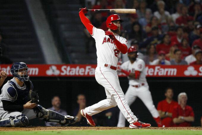 Los Angeles Angels' Jared Walsh follows through on a three-run home run next to New York Yankees catcher Gary Sanchez during the fourth inning of a baseball game in Anaheim, Calif., Tuesday, Aug. 31, 2021. (AP Photo/Alex Gallardo)