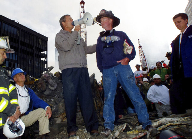 FILE - In this Sept. 14, 2001 file photo, as rescue efforts continue in the rubble of the World Trade Center in New York, President Bush stands with firefighter Bob Beckwith on a burnt fire truck in front of the World Trade Center during a tour of the devastation. In moments of crisis, American presidents have sought to summon words to match the moment in the hope that the power of oratory can bring order to chaos and despair.(AP Photo/Doug Mills, file)