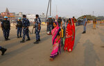 Hindu pilgrims walks past security officers standing guard in Ayodhya, India , Saturday, Nov. 9, 2019. India's security forces were on high alert ahead of the Supreme Court's verdict Saturday in a decades-old land title dispute between Muslims and Hindus over plans to build a Hindu temple on a site where Hindu hard-liners demolished a 16th century mosque in 1992, sparking deadly religious riots. (AP Photo/Rajesh Kumar Singh)