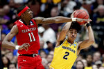 Michigan guard Jordan Poole, right, looks to pass the ball as Texas Tech forward Tariq Owens defends during the first half an NCAA men's college basketball tournament West Region semifinal Thursday, March 28, 2019, in Anaheim, Calif. (AP Photo/Jae C. Hong)