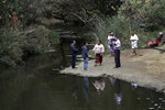 Visitors walk along Malibu Creek at the Malibu Creek State Park Thursday, Oct. 11, 2018, in Calabasas, Calif. Investigators will use ballistic testing to determine if a rifle carried by a burglary suspect was used in the killing of a camper at the California wilderness park. Authorities say 42-year-old Anthony Rauda had the gun and was dressed in black when he was arrested Wednesday after a search of a rugged canyon area near Malibu. (AP Photo/Marcio Jose Sanchez)