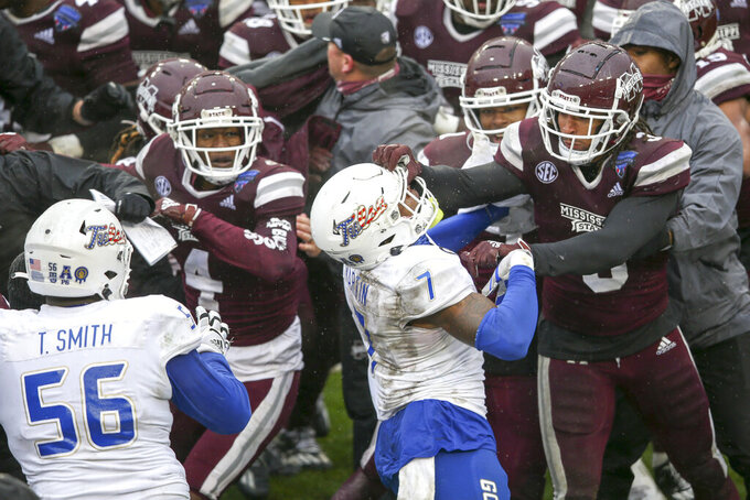 Mississippi State linebacker Aaron Brule (3) hits Tulsa safety TieNeal Martin (7) on the facemask during a postgame fight after Mississippi State's win in the Armed Forces Bowl NCAA college football game in Fort Worth, Texas, Thursday, Dec. 31, 2020. (Ian Maule/Tulsa World via AP)
