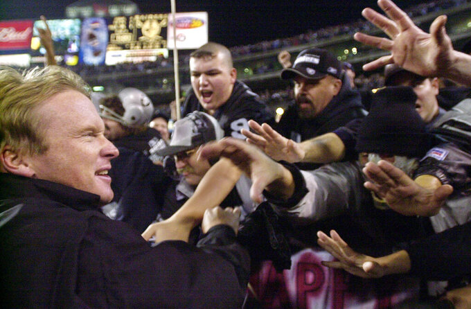 "FILE - In this Jan. 12, 2002, file photo, Oakland Raiders head coach Jon Gruden greets fans in the ""Black Hole"" after the Raiders beat the New York Jets 38-24 during the AFC Wildcard playoff NFL football game in Oakland, Calif. The Raiders' final scheduled game in Oakland on Sunday, Dec. 15, 2019, will be an emotional one for players and coaches, as well as fans. (AP Photo/Paul Sakuma, File)"