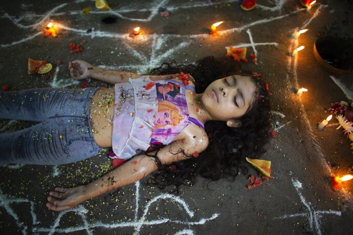 A girl lies surrounded by candles and designs of white powder during a ceremony on Sorte Mountain, Sunday, Oct. 13, 2019, where followers of indigenous goddess Maria Lionza gather annually in Venezuela's Yaracuy state. Believers congregated for rituals on the remote mountainside where devotees make an annual pilgrimage to pay homage to the goddess, seeking spiritual connection and physical healing. (AP Photo/Ariana Cubillos)
