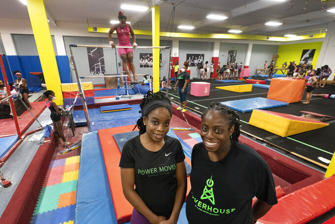 Candice Walker, left, and her sister Delissa, co-owners of Power Moves Gymnastics and Fitness, pose in their facility, Thursday, July 22, 2021, in Cedarhurst, N.Y. The business they started in 2012 was in a space so small it's now a barber shop. They moved to a warehouse in 2015 before opening at their current location last August in Cedarhurst, just east of New York City. (AP Photo/Mark Lennihan)