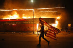 FILE - In this Thursday, May 28, 2020 file photo, a protester carries a U.S. flag upside down, a sign of distress, next to a burning building in Minneapolis. Protests over the death of George Floyd, a black man who died in police custody Monday, broke out in Minneapolis for a third straight night. (AP Photo/Julio Cortez)