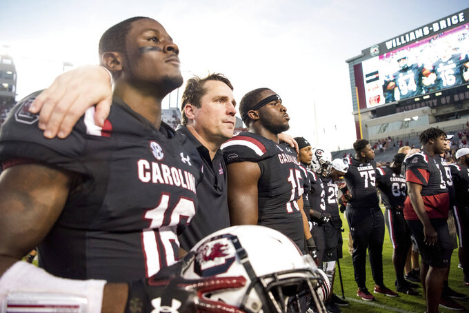 South Carolina head coach Will Muschamp, center, puts his arms around Rashad Fenton (16) and Aaron Sterling (15) after an NCAA college football game against Texas A&M Saturday, Oct. 13, 2018, in Columbia, S.C. Texas A&M defeated South Carolina 26-23. (AP Photo/Sean Rayford)