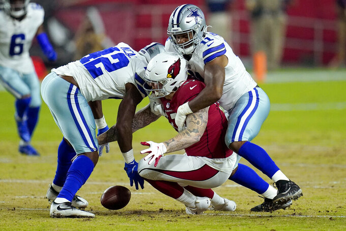 Dallas Cowboys linebacker Keanu Neal (42) strips the ball away from Arizona Cardinals tight end Maxx Williams, center, as Dallas Cowboys linebacker Micah Parsons, right, defends during the first half of an NFL preseason football game, Friday, Aug. 13, 2021, in Glendale, Ariz. (AP Photo/Ross D. Franklin)