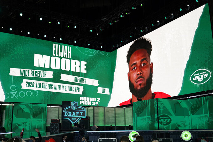 Images are displayed on stage of Elijah Moore, wide receiver at Mississippi, selected by the New York Jets in the second round of the NFL football draft, Friday, April 30, 2021, in Cleveland. (AP Photo/Tony Dejak)