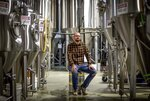 "Joel Iverson, chief operating officer of Monday Night Brewing, is photographed in the brewery that sits beside Reservoir No. 1, a 180 million-gallon water supply that has been out of service much of the past few decades, Oct. 15, 2019, in Atlanta. Iverson has previously noticed water trickling out of the hillside of the dam near the brewery he co-founded. ""If that one goes, it's going to wash away us and a lot of beer,"" said Iverson. (AP Photo/David Goldman)"