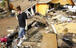 FILE - In this Sept. 24, 2008, file photo, Gina Hadley walks through what's left of her home in the aftermath of Hurricane Ike in Galveston, Texas. The Ike Dike is a proposed coastal barrier that would protect the Houston-Galveston region, including Galveston Bay, from hurricane storm surge. The project was conceived by Bill Merrell, a professor in the Marine Sciences Department at Texas A&M University at Galveston and a former president of the school, in response to the extensive surge damage caused by Hurricane Ike in September of 2008. (AP Photo/David J. Phillip, File)
