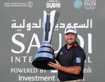 Graeme McDowell from Northern Ireland celebrates with the trophy after he wins the final round of the Saudi International at Royal Greens Golf and Country Club, Sunday, Feb. 2, 2020, in Red Sea resort of King Abdullah Economic City, Saudi Arabia. (AP Photo/Amr Nabil)