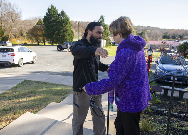 """In this Nov. 17, 2020, photo, Maria Edgar, right, hugs Joseph Sirko who rescued her from her vehicle after she was caught in flooding on Brooke Road, in Stafford, Va. In a heavy downpour Nov. 12, Edgar, 74, left her Marlborough Point home in her Toyota Prius for a doctor's appointment. She drove past a """"road closed"""" sign into an area where high water always accumulates during heavy rain. Soon her Prius was floating uncontrollably in the current. (Mike Morones/The Free Lance-Star via AP)"""