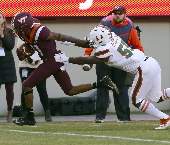 Virginia Tech's Tre Turner (11) escapes Miami defender Shaquille Quarterman (55) on the way to a 20 yard touchdown run during the first half of an NCAA college football game in Blacksburg, Va., Saturday, Nov. 17 2018. (Matt Gentry/The Roanoke Times via AP)