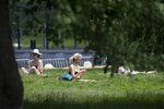 FILE - In this Thursday, June 18, 2020 file photo, people sit on the grass in Gorky Park in Moscow, Russia during a heat wave. An overheating world obliterated weather records in 2020 — an extreme year for hurricanes, wildfires, heat waves, floods, droughts and ice melt — the United Nations' weather agency reported Wednesday, Dec. 2, 2020. (AP Photo/Alexander Zemlianichenko)