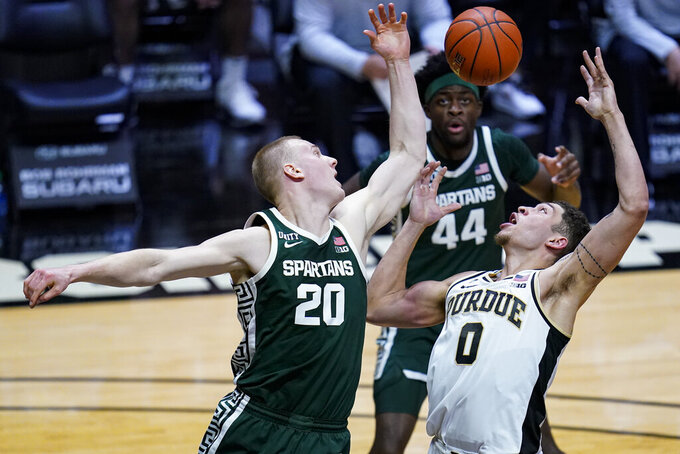 Purdue forward Mason Gillis (0) and Michigan State forward Joey Hauser (20) go up for a rebound during the second half of an NCAA college basketball game in West Lafayette, Ind., Tuesday, Feb. 16, 2021. (AP Photo/Michael Conroy)