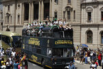 Rugby fans follow the bus of the South African Springbok rugby team, during a victory parade in Pretoria, South Africa, Thursday, Nov. 7, 2019. South Africa's Rugby World Cup-winning team have started a five-day victory tour where they will carry the trophy across the country. South Africa beat England in Saturday's final in Japan to clinch a third World Cup title.  (AP Photo/Themba Hadebe)