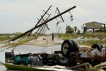 FILE - In this Thursday, Aug. 27, 2020 file photo, people survey the damage left in the wake of Hurricane Laura in Holly Beach, La. A hotter world is getting closer to passing a temperature limit set by global leaders five years ago and may exceed it in the next decade or so, according to a new United Nations report released on Wednesday, Sept. 9, 2020. (AP Photo/Eric Gay)