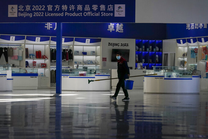 """A cleaner wearing a face mask to curb the spread of the coronavirus walks by a Beijing Winter Olympics merchandise store inside the Olympics Tower in Beijing on Tuesday, Feb. 2, 2021. The 2022 Beijing Winter Olympics will open a year from now. Most of the venues have been completed as the Chinese capital becomes the first city to hold both the Winter and Summer Olympics. Beijing held the 2008 Summer Olympics. But these Olympics are presenting some major problems. They are already scarred by accusations of rights abuses including """"genocide""""against more than 1 million Uighurs and other Muslim ethnic groups in western China. (AP Photo/Andy Wong)"""