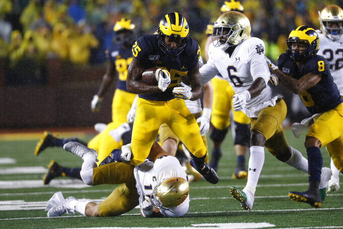 Michigan running back Hassan Haskins (25) runs over Notre Dame safety Alohi Gilman (11) during a 20-yard gain in the first half of an NCAA college football game in Ann Arbor, Mich., Saturday, Oct. 26, 2019. (AP Photo/Paul Sancya)