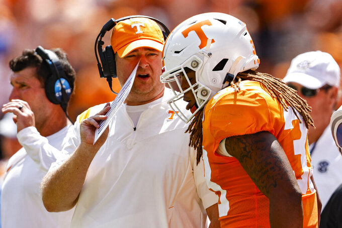 Tennessee head coach Josh Heupel talks to linebacker Jeremy Banks (33) after he was called for unnecessary roughness during the first half of an NCAA college football game against Pittsburgh, Saturday, Sept. 11, 2021, in Knoxville, Tenn. (AP Photo/Wade Payne)