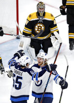 Winnipeg Jets left wing Kyle Connor (81) is congratulated by center Mark Scheifele (55) after his second goal of the period off Boston Bruins goaltender Jaroslav Halak, rear, during the third period of an NHL hockey game in Boston, Tuesday, Jan. 29, 2019. (AP Photo/Charles Krupa)