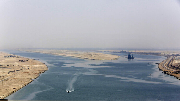 FILE - In this Aug. 6, 2015 file photo, an army zodiac secures the entrance of the new section of the Suez Canal in Ismailia, Egypt. The Suez Canal, which connects the Red Sea to the Mediterranean Sea, revolutionized maritime travel by creating a direct shipping route between the East and the West. But as Egypt marks the 150th anniversary of its opening, marine biologists are bemoaning one of the famed waterway's lesser known legacies, the invasion of hundreds of non-native species that have driven the native marine life toward extinction and altered the delicate Mediterranean ecosystem with potentially devastating consequences. (AP Photo/Amr Nabil, File)
