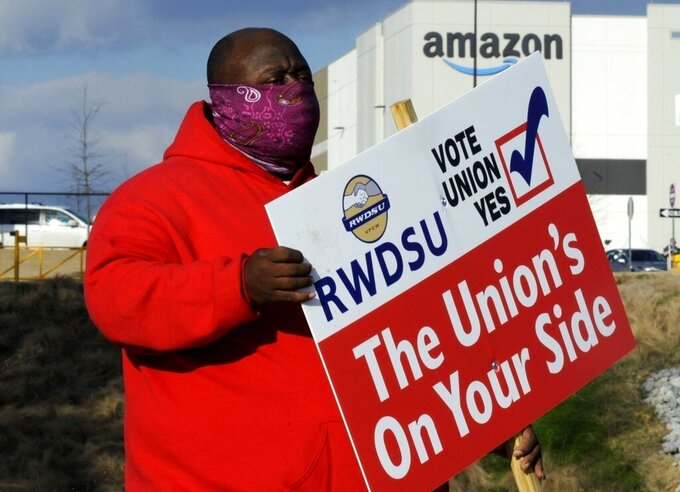 FILE - In this Tuesday, Feb. 9, 2021, file photo, Michael Foster of the Retail, Wholesale and Department Store Union holds a sign outside an Amazon facility where labor is trying to organize workers in Bessemer, Ala. Nearly 6,000 Amazon warehouse workers in Bessemer, Alabama, have voted on whether or not to form a union. But the process to tally all the ballots and determine an outcome will continue for a second week, according to the National Labor Relations Board, a government agency that's conducting the election.(AP Photo/Jay Reeves, File)