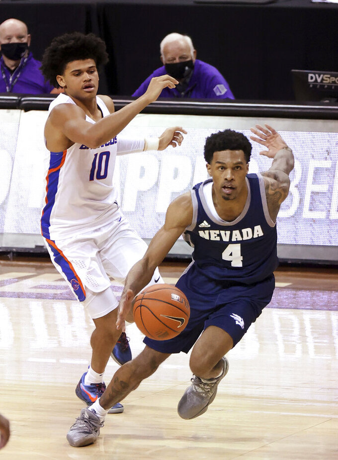 Nevada guard Desmond Cambridge Jr. (4) drives as Boise State guard RayJ Dennis (10) defends during the second half of an NCAA college basketball game in the quarterfinals of the Mountain West Conference men's tournament Thursday, March 11, 2021, in Las Vegas. (AP Photo/Isaac Brekken)