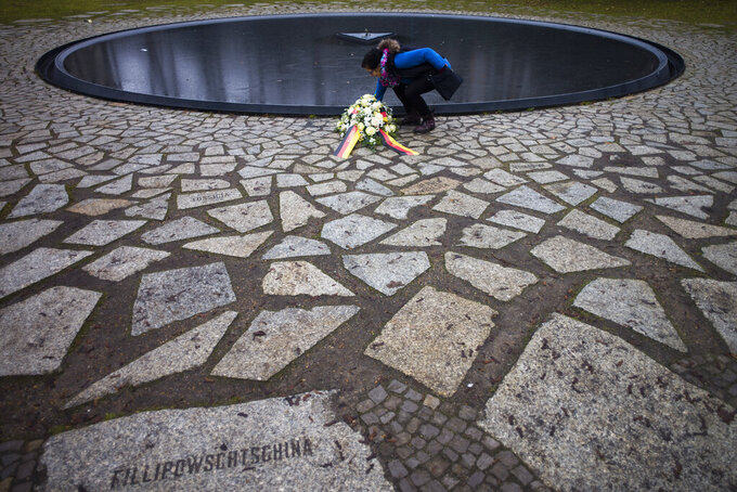 A woman adjust flowers at the Memorial to the Sinti and Roma Victims of the Holocaust on the International Holocaust Remembrance Day, in Berlin, Germany, Wednesday,, Jan. 27, 2021. (AP Photo/Markus Schreiber)
