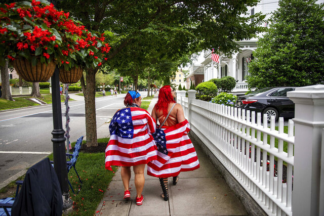 Parade goers draped in American flags walk down the street before a Fourth of July parade begins Saturday, July 4, 2020, in Bristol, R.I. The town, which lays claim to the nation's oldest Independence Day celebration in the country, held a vehicle-only scaled down version of its annual parade Saturday due to the coronavirus pandemic. (AP Photo/David Goldman)