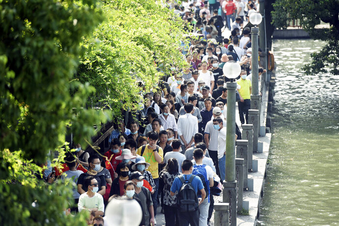 Tourists crowd along a waterfront path at the West Lake in Hangzhou in eastern China's Zhejiang Province, Thursday, Oct. 1, 2020. Millions of Chinese tourists usually would use their week-long National Day holidays to travel abroad. This year, travel restrictions due to the coronavirus pandemic mean that some 600 million tourists - about 40% of the population - will travel within China during the holiday that began Thursday, according to Ctrip, China's largest online travel agency. (Chinatopix via AP)