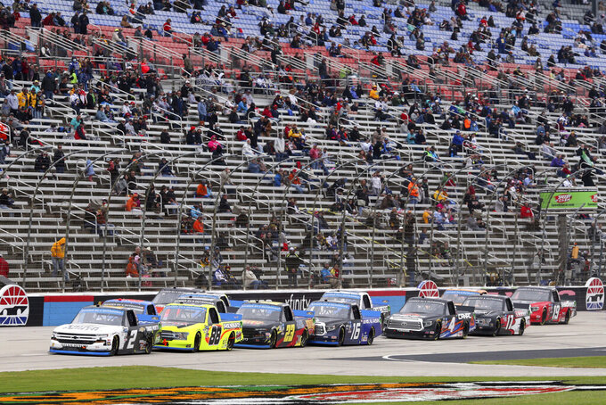 NASCAR Texas Trucks Series trucks resume racing after a caution during an auto race at Texas Motor Speedway in Fort Worth, Texas, Sunday, Oct. 25, 2020. (AP Photo/Richard W. Rodriguez)