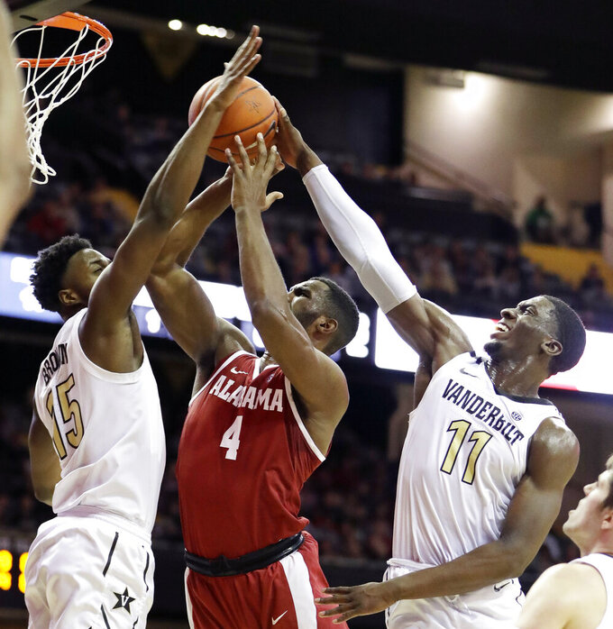 Alabama forward Daniel Giddens (4) shoots between Vanderbilt defenders Clevon Brown (15) and Simisola Shittu (11) in the first half of an NCAA college basketball game, Saturday, Feb. 9, 2019, in Nashville, Tenn. (AP Photo/Mark Humphrey)