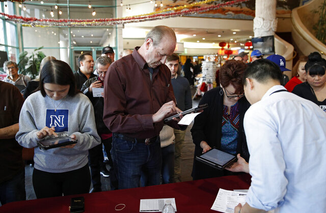 FILE - In this Feb. 15, 2020, file photo sign in on tablet computers at an early voting location in the Chinatown Plaza, in Las Vegas. Nevada Democrats are hoping to avoid a repeat of the chaos that ensnared the Iowa caucuses, as voters gather across the Silver State on Saturday to make their presidential preferences known. Iowa's process cratered this month following a rushed effort by state Democrats to deploy a mobile app for caucus volunteers to report results. Democrats in Nevada were going to use the same app developer as Iowa did, but quickly sidelined those plans. They will still be relying to some extent on technology to assist in counting and reporting results, though, and like Iowa, they will have paper backups. (AP Photo/John Locher, File)