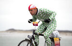 A competitor wearing a onesie with Brussels sprouts battles gale force winds during the Dutch Headwind Cycling Championships on the storm barrier Oosterscheldekering near Neeltje Jans, south-western Netherlands, Sunday, Feb. 9, 2020. (AP Photo/Peter Dejong)