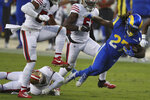 Los Angeles Rams running back Darrell Henderson Jr. (27) falls forward as he is tackled by San Francisco 49ers free safety Jimmie Ward, bottom left, during the first half of an NFL football game in Santa Clara, Calif., Sunday, Oct. 18, 2020. (AP Photo/Jed Jacobsohn)