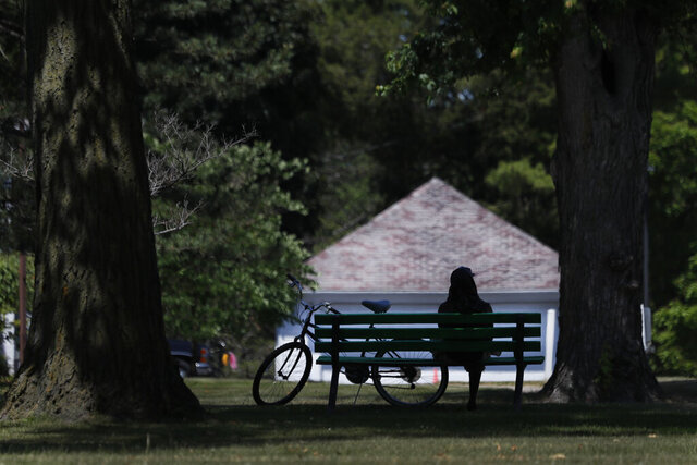 FILE - In this June 29, 2020 file photo, a cyclist sits on a Hoyt Park bench in Saginaw, Mich. It has been months since many people first learned what a shelter-in-place order even meant. As restrictions are slowly lifted, it's now time to reflect. This is a meaningful opportunity to learn from what we've all experienced. Experts explore some of the financial repercussions of this pandemic, including what Americans have been learning in the process, and how they'll likely apply these lessons to life after the outbreak is over.  (AP Photo/Charles Rex Arbogast, File)