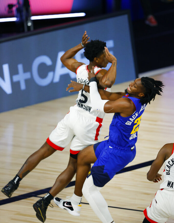 Toronto Raptors' Stanley Johnson (5), left, collides with Denver Nuggets' Tyler Cook (25) during the third quarter of an NBA basketball game Friday, Aug. 14, 2020, in Lake Buena Vista, Fla. (Mike Ehrmann/Pool Photo via AP)
